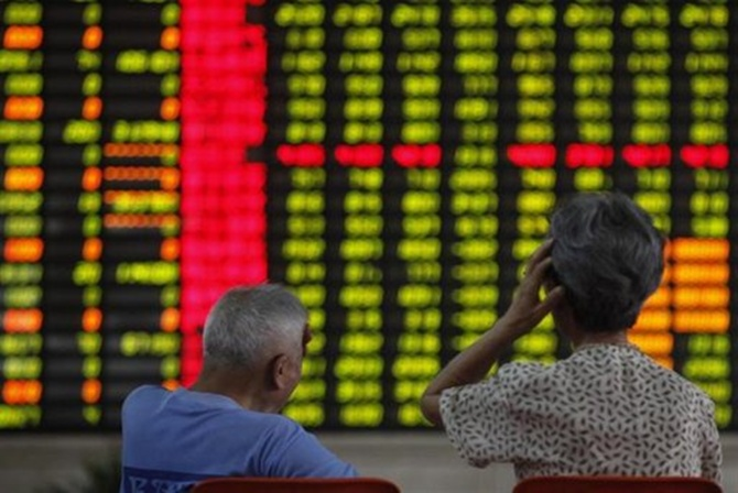 Investors sit in front of an electronic board showing stock information at a brokerage house in Shanghai.