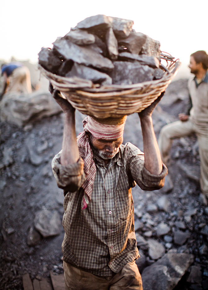 A villager carries a basket of coal scavenged illegally from an open-cast mine in the village of Jina Gora near Jharia.