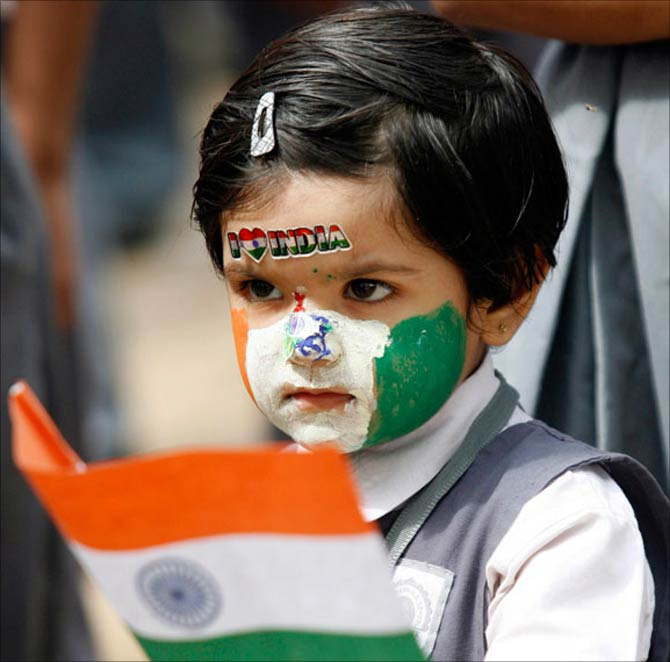 A girl with her face painted in colours of the Indian national flag.