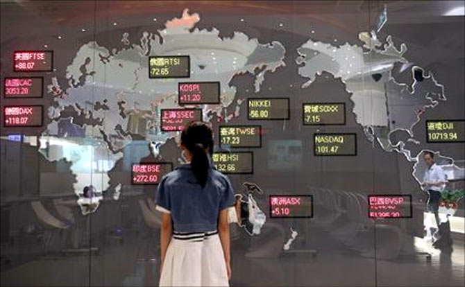 A girl looks at a board showing global stock indices at the Taiwan Stock Exchange in Taipei.