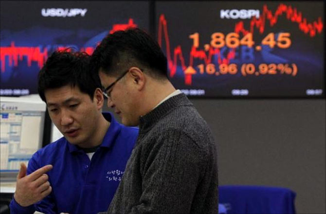Foreign currency dealers from the Korea Exchange Bank are seen in front of a monitor displaying the current Korea Composite Stock Price Index (KOSPI) at the KEB in Seoul.