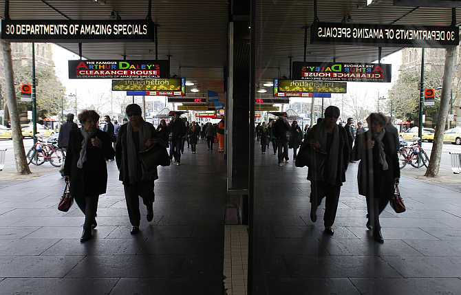 Pedestrians walk past shops in central Melbourne, Australia.