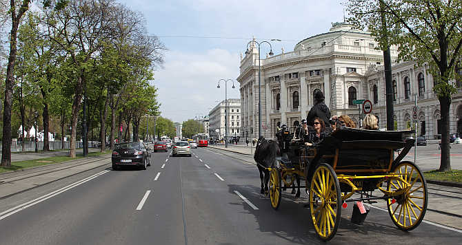 A traditional Fiaker horse carriage passes Burgtheater theatre on Dr-Karl-Lueger-Ring street in Vienna, Austria.