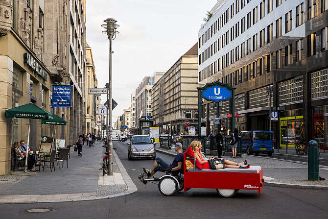 Tourists Caro and Anna from Munich lie in a bed mounted to a rental bike as they ride along Friedrichstrasse in central Berlin, Germany.