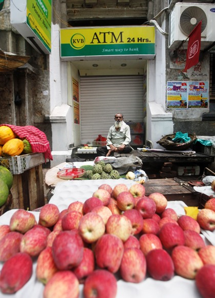 A roadside vendor selling fruits sits in front of a closed automated teller machine counter during a two-day strike in Kolkata.