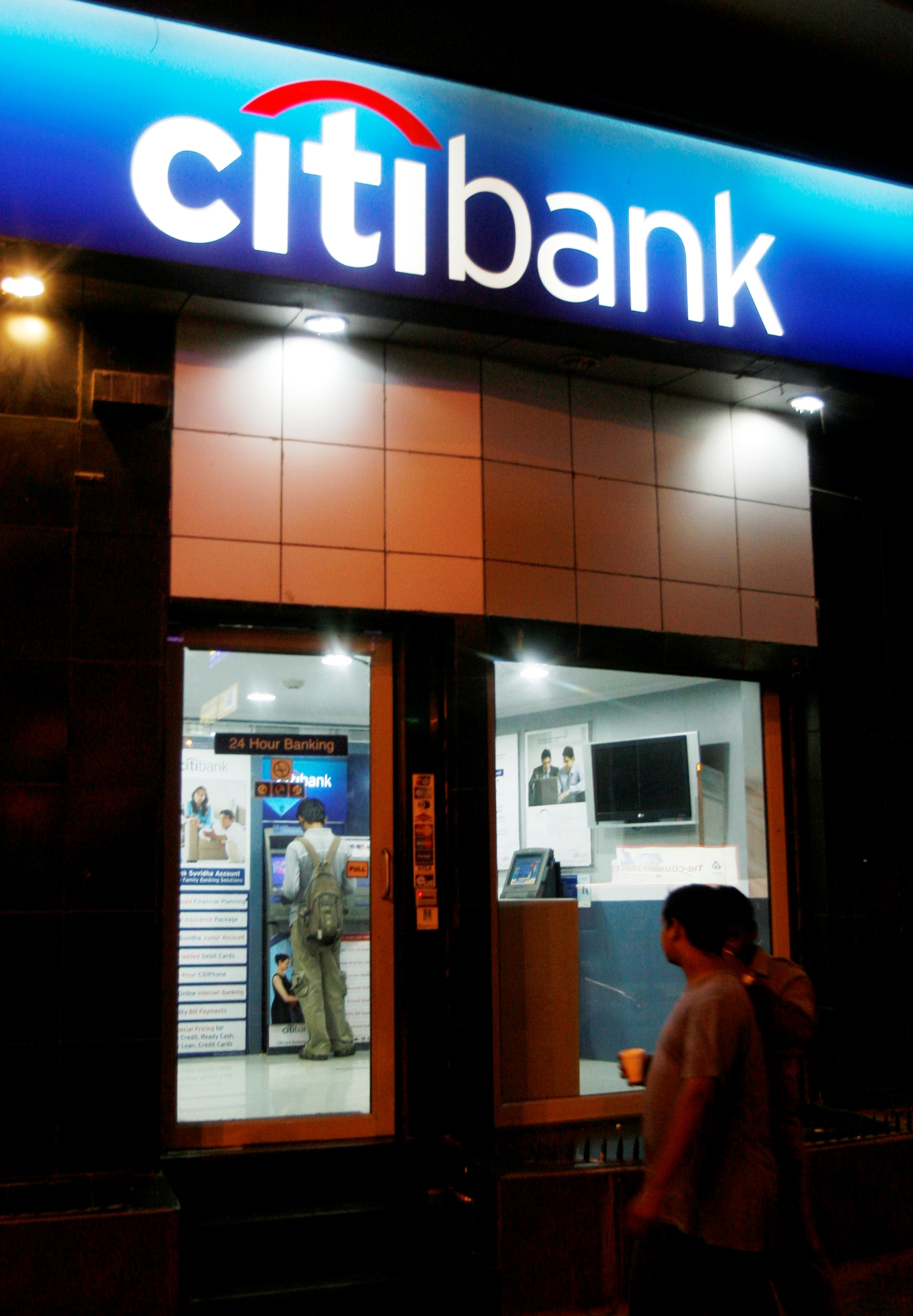 People walk past an ATM counter of Citibank in Mumbai.