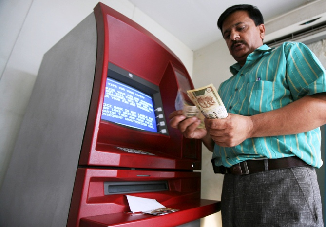 A man counts money after withdrawing it from an ATM.
