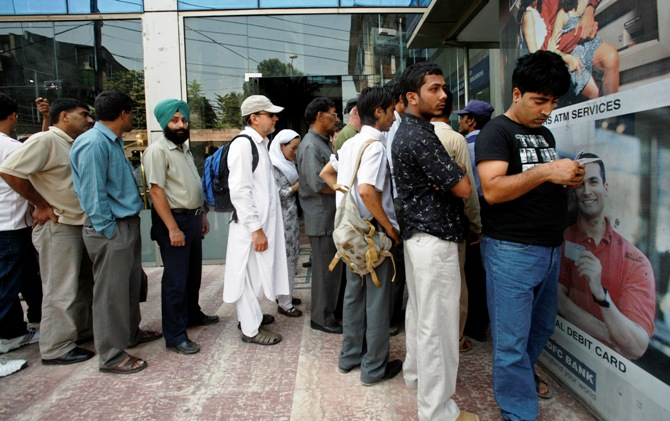 People wait in line outside an ATM to withdraw money in Srinagar.