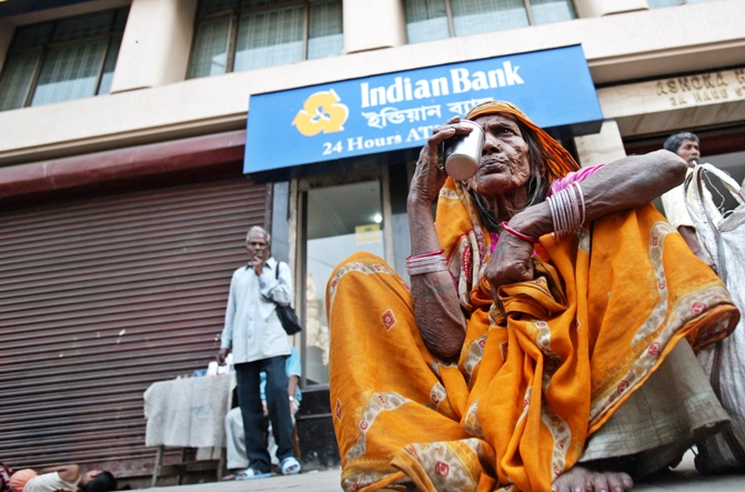 A homeless Indian woman sits outside a bank's ATM kiosk in Kolkata.