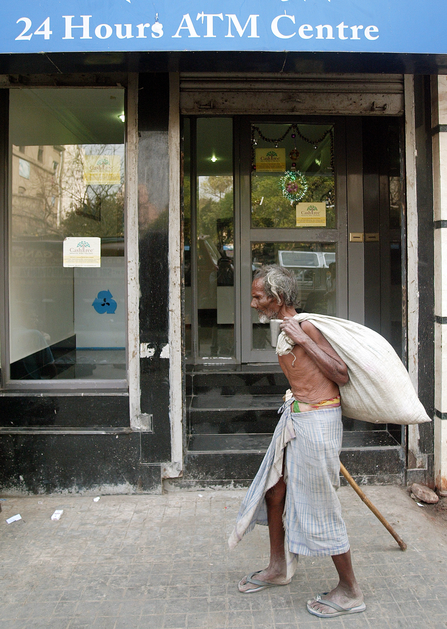 A homeless Indian man walks past a bank's ATM kiosk in Kolkata.