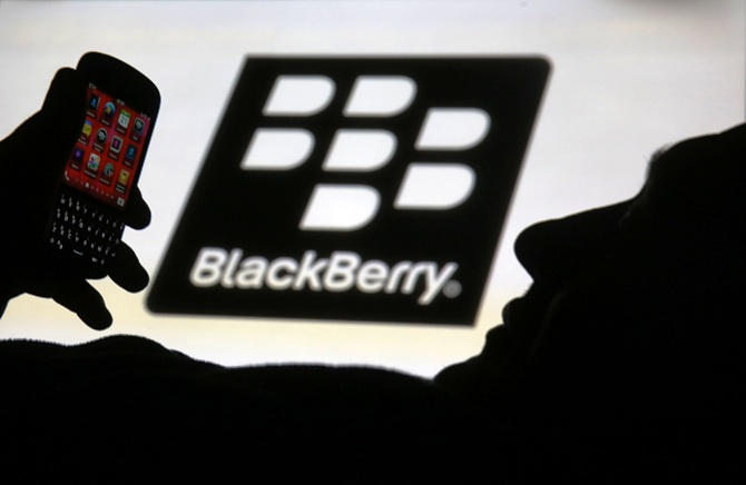 A man is silhouetted against a video screen with the Blackberry logo as he poses with a Blackberry Q10 in this photo illustration.
