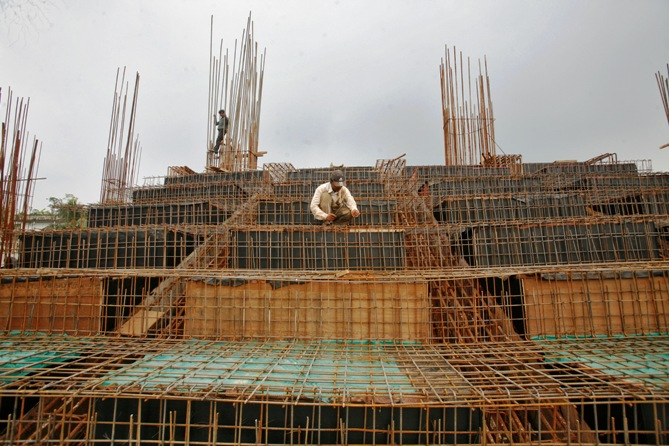 Labourers work at the construction site of a stadium on the outskirts of Agartala.