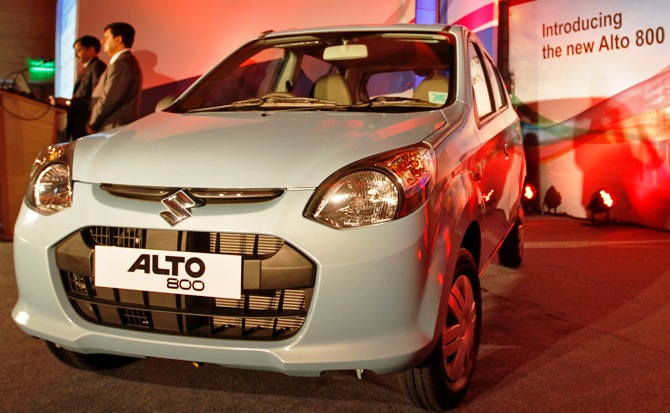 Officials stand next to the newly launched Maruti Suzuki Alto 800 car in Ahmedabad.