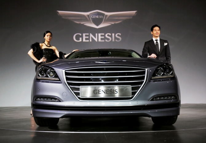 Models pose with Hyundai Motor's new Genesis sedan during a photo session at a hotel in Seoul, November 26, 2013.