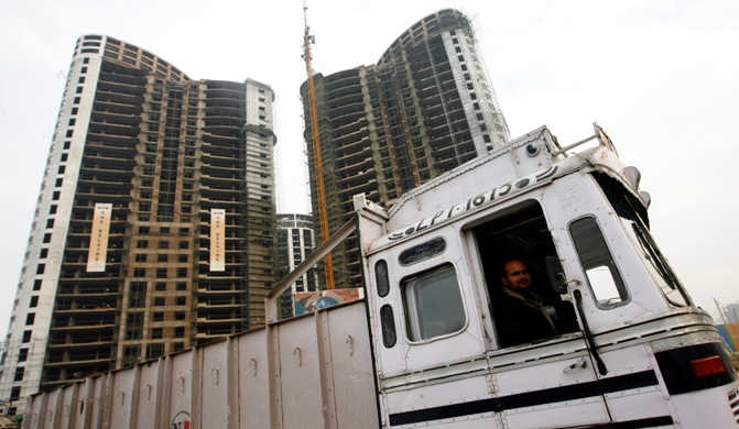 A truck driver looks out at the construction site of a residential apartment building in Gurgaon.