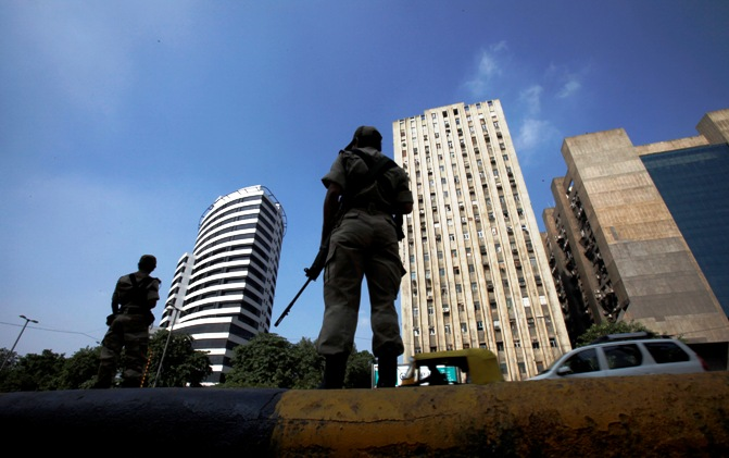 ndian paramilitary soldiers stand guard on a roadside against the backdrop of high-rise buildings in New Delhi.