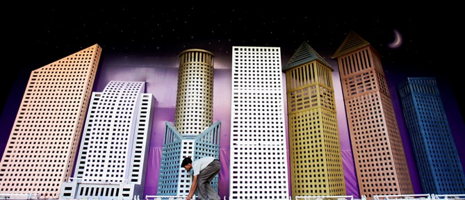 A worker adjusts decorative lights on a model of skyscrapers representing the future of Mumbai city.