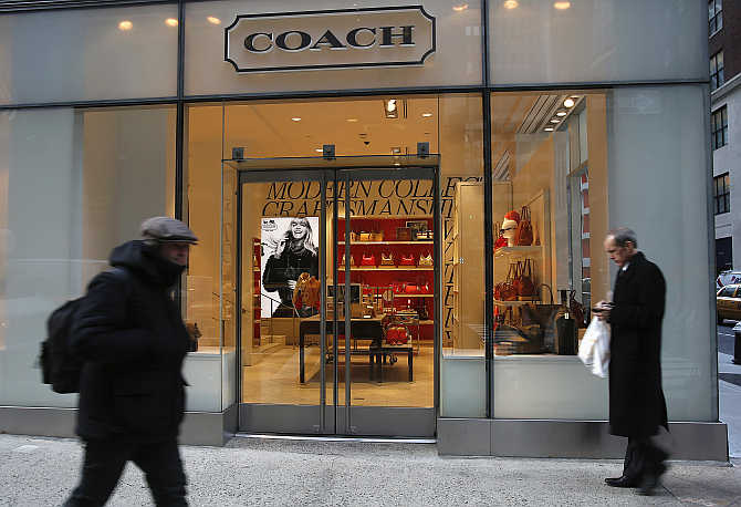 People walk past a Coach store on Madison Avenue in New York, United States.