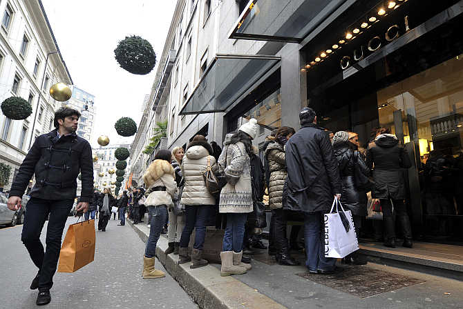 A passer-by looks on as shoppers queue up outside a Gucci shop in downtown Milan, Italy.