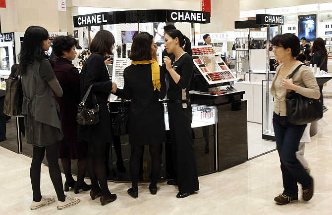 Customers choose cosmetics at a Chanel counter at the Shinsegae department store in Seoul, South Korea.