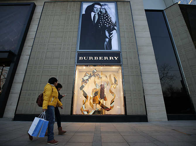 People walk past the window display of a Burberry store in Beijing, China.