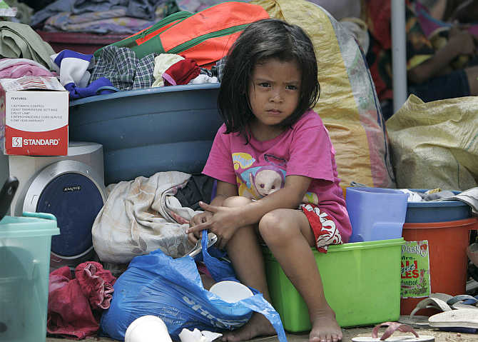 A girl sits on her belongings after a fire razed hundreds of houses and left more than a thousand families homeless at a slum area in Mandaluyong City in Manila, the Philippines.
