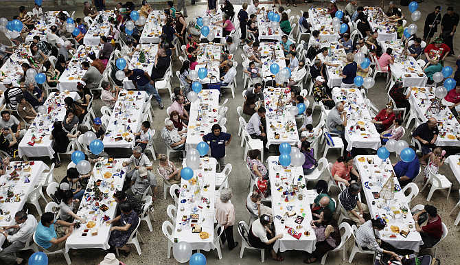 People sit down for a Christmas Day lunch served by more than 200 volunteers at a converted train works