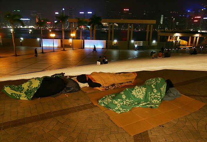 Homeless people sleep outside the Hong Kong Cultural Centre.