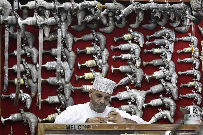 A man sits in front of a display of jambiyas (traditional daggers) in Mattrah Souq, the oldest market in Oman, in the capital Muscat.
