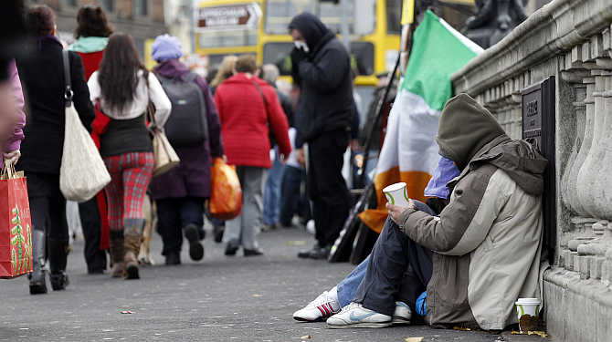 Homeless people beg for money on O'Connell bridge in central Dublin, Ireland.