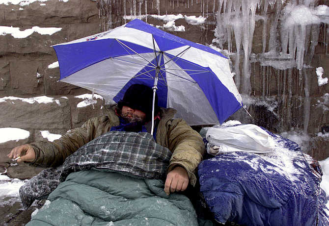 A homeless man uses an umbrella to protect himself from falling and melting ice in Toronto's financial district, Canada.