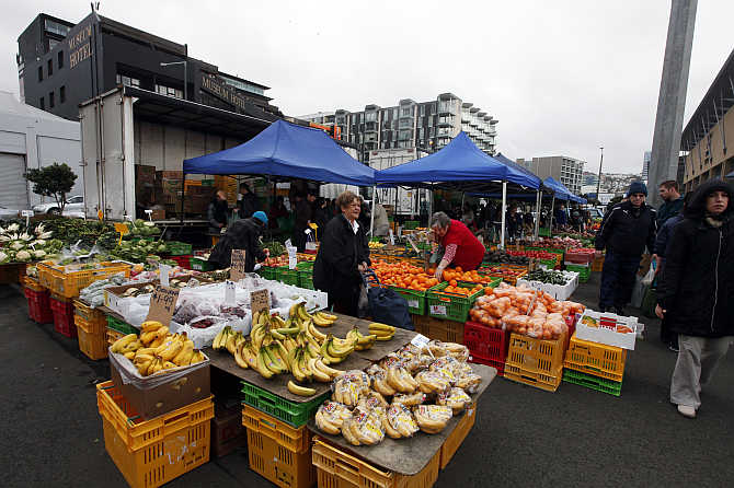 People buy fruits at a market in Wellington, New Zealand.