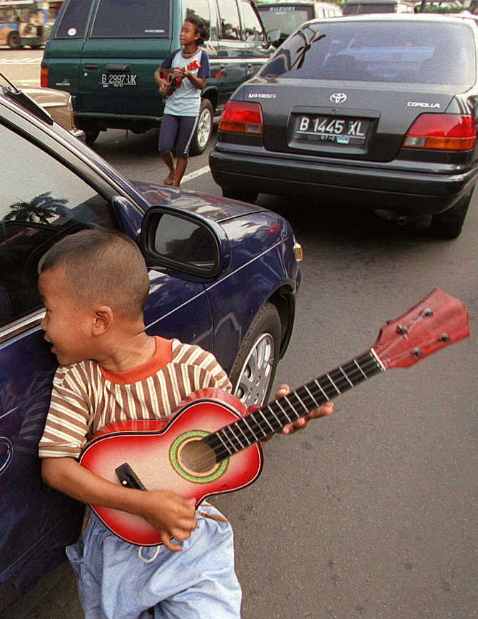A six-year-old boy carries a small guitar as he begs on the streets of central Jakarta, Indonesia.