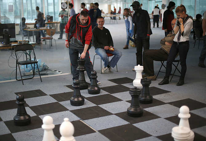 A guest plays chess with a volunteer, right, in a temporary Christmas shelter for homeless people in east London, United Kingdom.