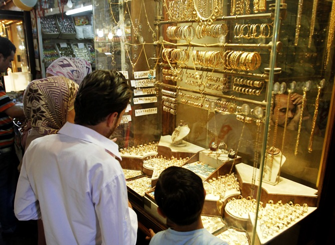 Customers stand in front of a gold shop.