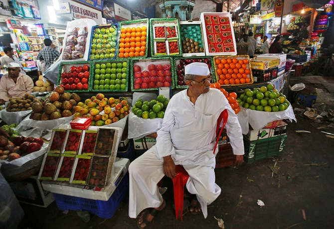 A fruit seller waits for customers at his stall at a wholesale market in Mumbai.