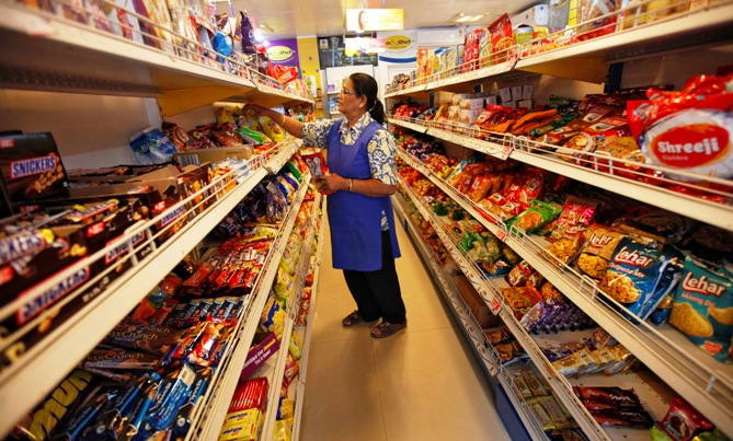 A worker arranges food packets inside a retail store in Kolkata.