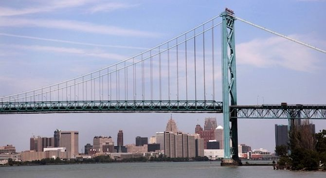 The Detroit city skyline is seen behind the Ambassador Bridge, an international border-crossing linking Windsor, Ontario with Detroit, along the Detroit River in Detroit, Michigan.