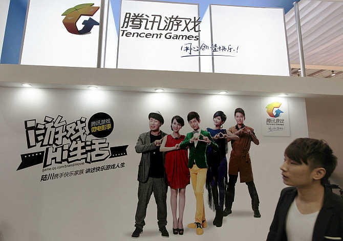 A man walks past a booth of Tencent Games during the China International Digital Content Expo in Beijing.