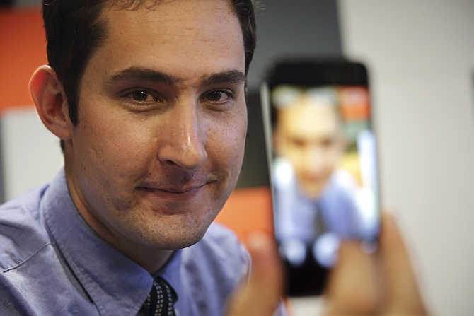 Kevin Systrom, CEO, Instagram, the popular photo-sharing app now owned by Facebook, displays his photo on a mobile phone at the LeWeb technology conference in Aubervilliers, near Paris, France.