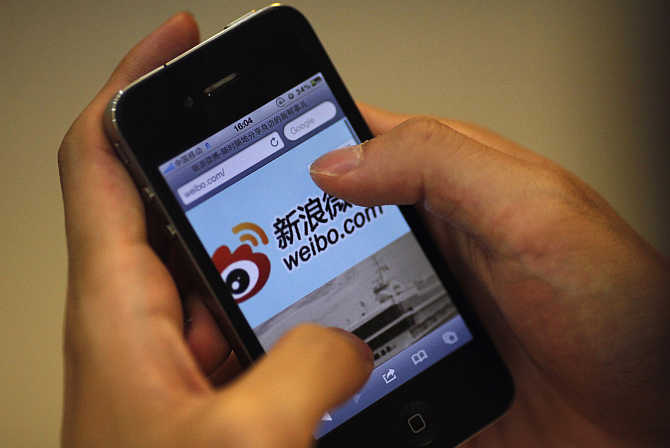 A man holds an iPhone as he visits Sina's Weibo microblogging site in Shanghai.