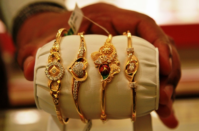 The salesman displays gold bangles to a customer at a jewellery showroom in Chennai.