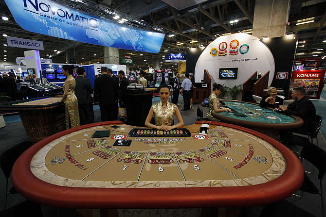 A croupier sits in front of a gaming table at Global Gaming Expo Asia in Macau.