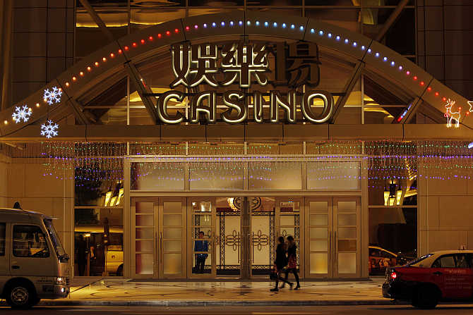 People walk past an entrance to a casino in Macau.