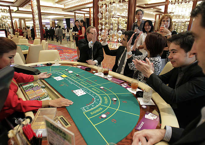 Foreigners play on a baccarat table during the opening of Solaire Casino-Resort in Pasay city, Metro Manila, the Philippines.