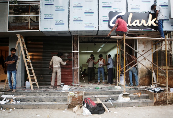 Men work at the site of a new shoe store.