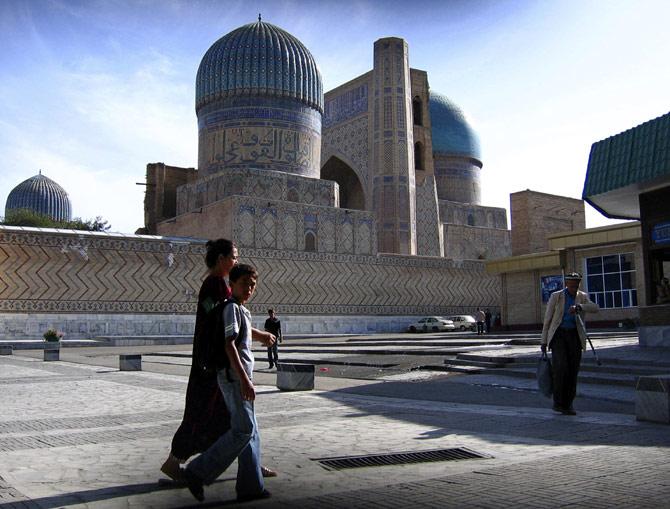 Pedestrians walk past Bibi Khanum mosque.