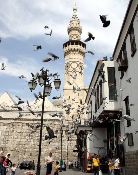 Pigeons fly in front of the historical Umayyad mosque in old Damascus city.