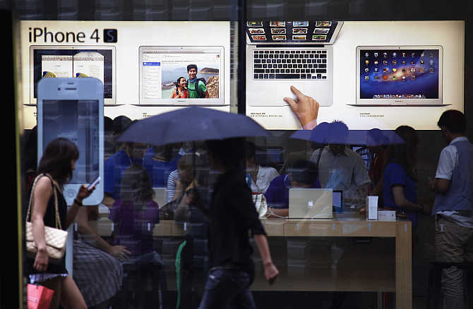 A woman uses an iPhone as she and other pedestrians walk past an Apple store in Beijing, China.