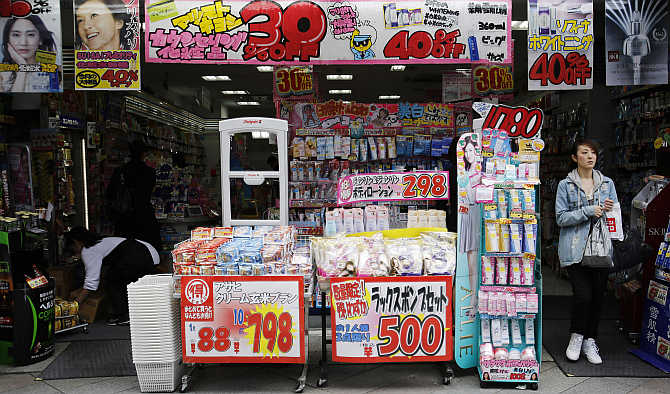 A woman walks out of a drugstore in Tokyo, Japan.